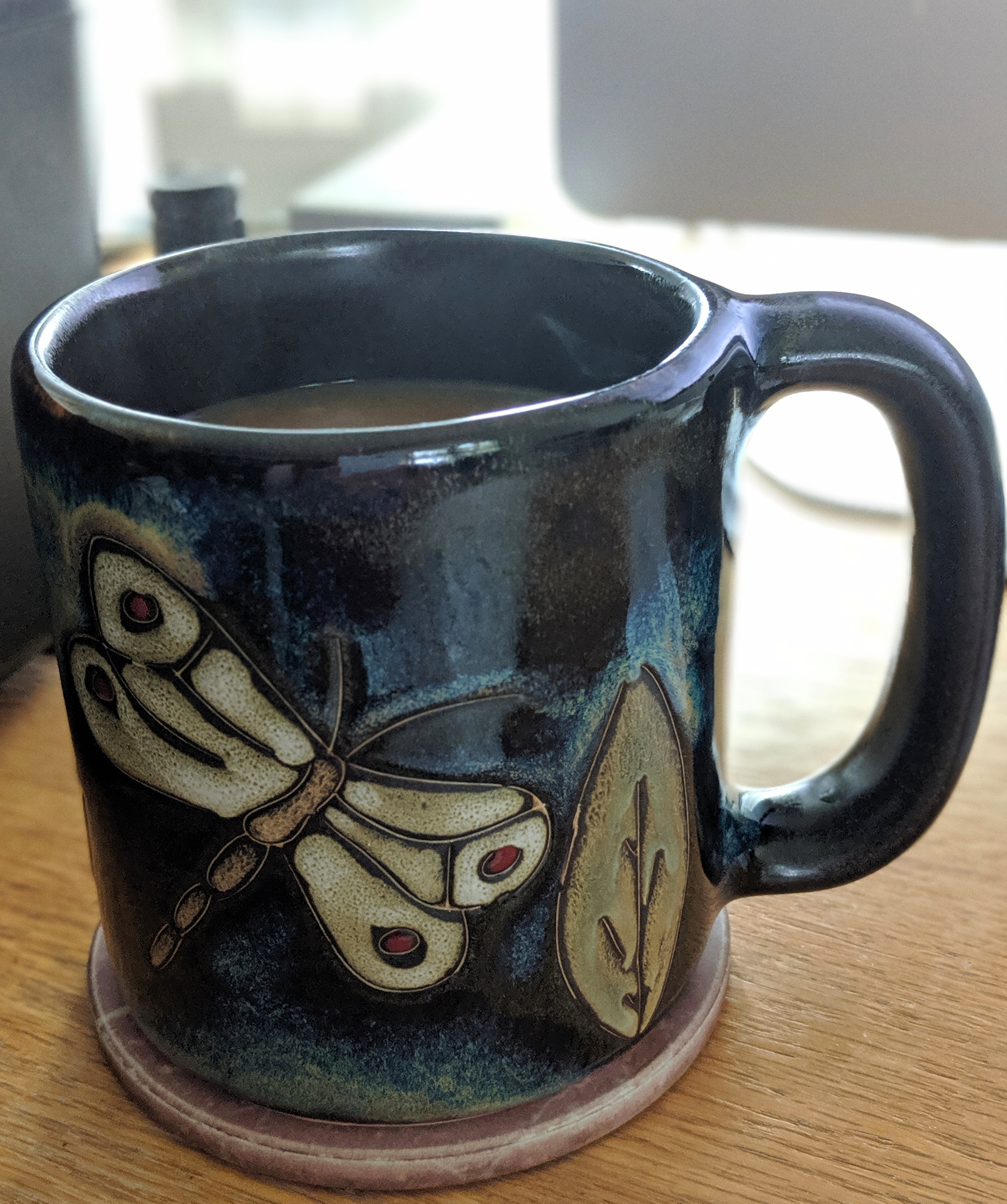 Photo of dragonfly coffee mug on a coaster on my desk.